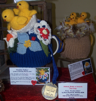 two tea cosies with chicken decorations and the winning medal for the animal section